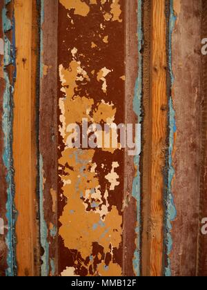 Background of weathered rustic wood with dark red, orange and light blue paint peeling off as background - Stock Photo