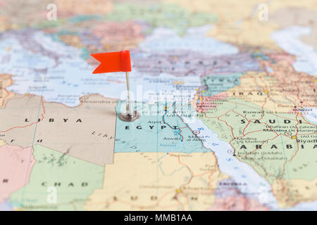 Small red flag marking the African country of  Egypt on a world map. - Stock Photo