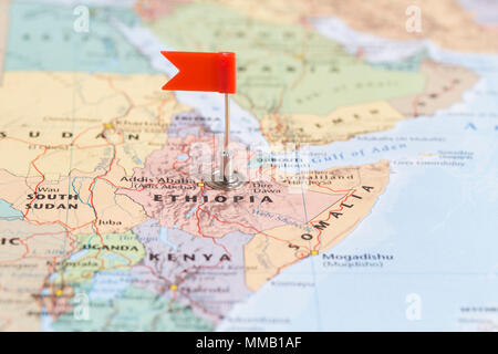 Small red flag marking the African country of  Ethiopia on a world map. - Stock Photo