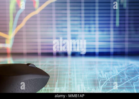 Computer mouse on futuristic display with defocused stock market graphs. Internet trading and modern business theme - Stock Photo