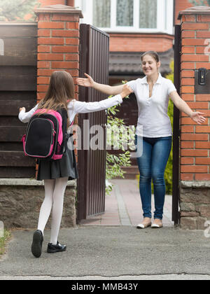 Happy cheerful girl running and hugging her mother after school - Stock Photo