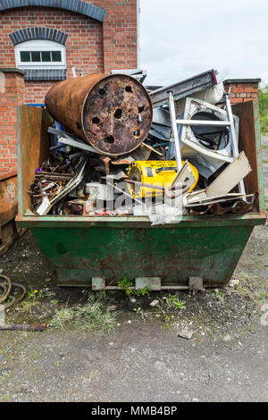 Skip or dumpster filled with waste metal ready for collection - Stock Photo