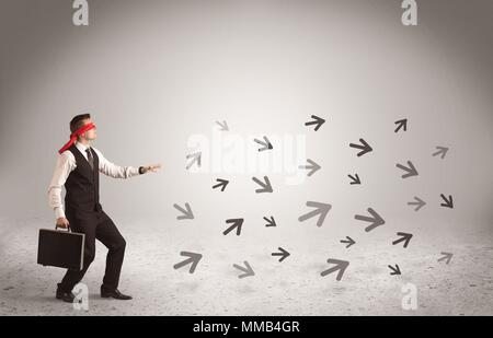 A male office worker standing blindfolded and confused with arrows pointing in different directions concept - Stock Photo