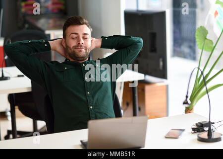 Young man studying with laptop computer on white desk. Attractive guy with beard wearing casual clothes taking a break. - Stock Photo