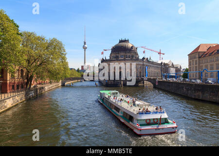 People visiting the city of Berlin with a touristic ship, at museum island with TV tower in the background - Stock Photo