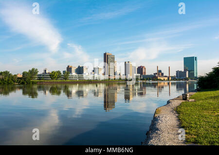 A panoramic view of downtown Toledo Ohio's skyline from across the Maumee River.  A beautiful blue sky with white clouds reflecting into the water. - Stock Photo