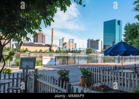 A panoramic view of downtown Toledo Ohio's skyline from across the Maumee River at a popular restaurant area with a paver brick boardwalk. - Stock Photo