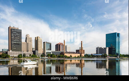 A panoramic view of downtown Toledo Ohio's skyline reflecting into the Maumee River with a power boat cruising by.  A beautiful  blue sky. - Stock Photo