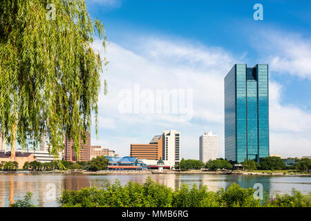 A panoramic view of downtown Toledo Ohio's skyline from across the Maumee River.  A beautiful  blue sky with white clouds for a backdrop. - Stock Photo