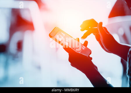 Business people using smartphone with to looking business chart on screen - Stock Photo