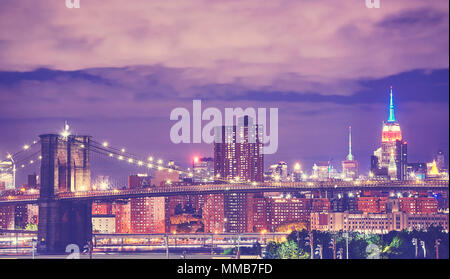 Vintage toned picture of the Brooklyn Bridge and Manhattan skyline at night, New York City, USA. - Stock Photo