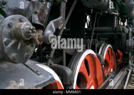 fragment of vintage functioning steam locomotive with leading wheels, piston and levers - Stock Photo
