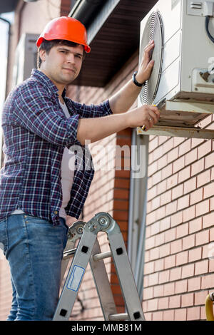 Portrait of male repairman standing on stepladder and repairing air conditioner - Stock Photo