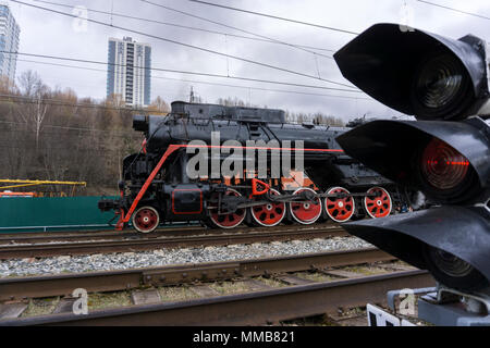 vintage locomotive leaves because of a traffic light in the foreground on the modern railway station - Stock Photo