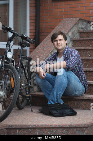 Smiling young man sitting on house porch and repairing bicycle - Stock Photo