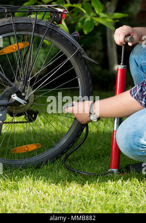 Closeup image of man connecting air pump to valve on bicycle wheel - Stock Photo