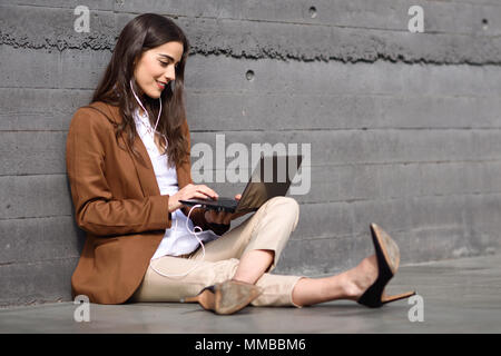 Young businesswoman sitting on floor looking at her laptop computer. Beautiful woman wearing formal wear using earphones. - Stock Photo
