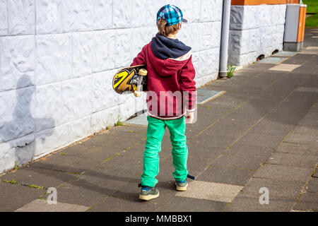 Young walking along white wall with longboard. - Stock Photo