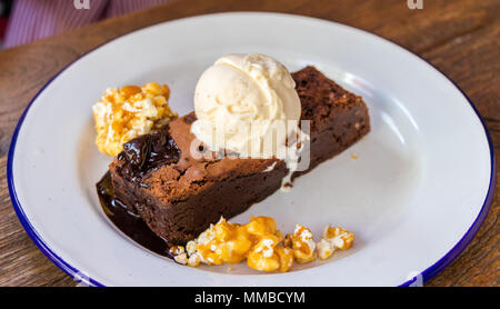 Delicious brownie with a scoop of vanilla ice cream. - Stock Photo