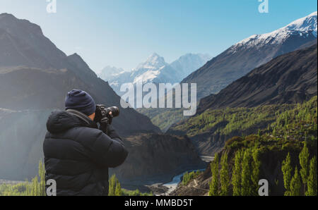 Photographer taking photograph of Hunza valley landscape in Pakistan by dslr camera - Stock Photo