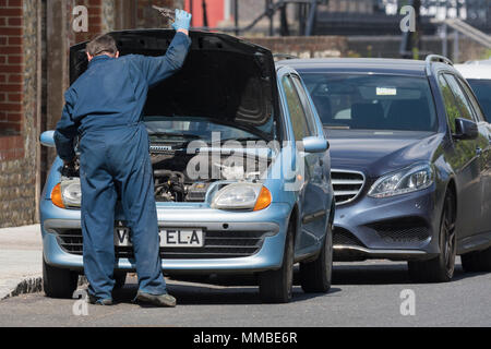 Car mechanic wearing overalls working on a car with the bonnet up in the UK.