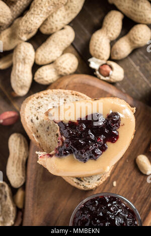 Peanut Butter and Jelly Sandwich on Rustic Wooden Background. Homemade Healthy Breakfast. - Stock Photo