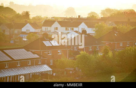 The sun rises over the Wiltshire village of Edington, village homes in the early morning orange light. - Stock Photo