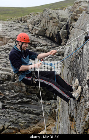 Climbers club climbing and abseiling on cliffs next to the sea. A variety of young and old participants - Stock Photo