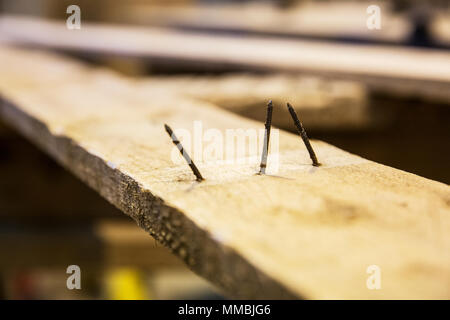 Close up of three rusty nails sticking out of a wooden plank. - Stock Photo