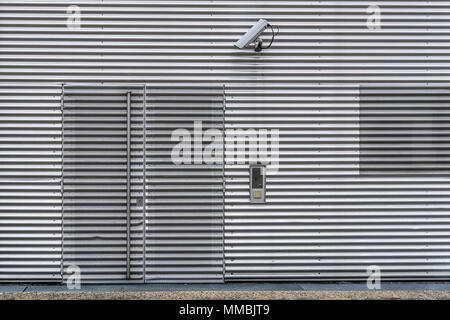 Exterior video surveillance and security system with CCTV camera on a corrugated iron wall to watch over the entrance of the building. - Stock Photo
