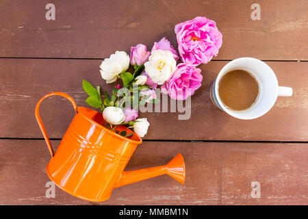 Bouquet of pink white roses in a vase, watering can and a cup of coffee on a wooden table. Home interior with coffee and flowers. Summer morning concept - Stock Photo