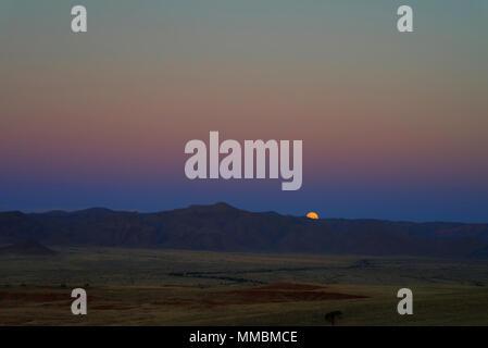 Full moon ascends over the dune in Namib desert - Stock Photo