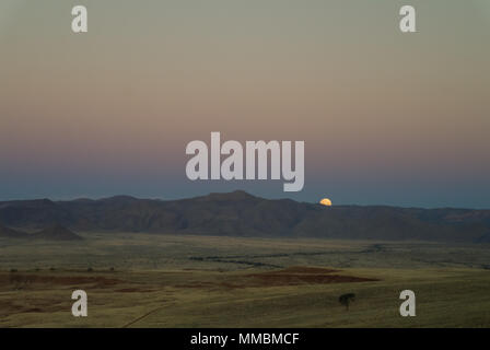 Full moon ascends over the dune in Namib desert, Namibia - Stock Photo