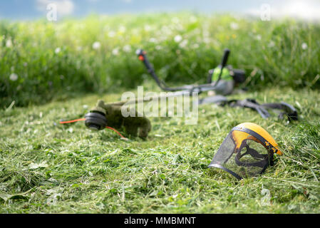String trimmer and protective face mask on mown grass, growing grass and the blue sky on the background - Stock Photo