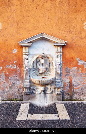 Small drinking fountain with sculpture and stone decor in shabby painted wall, Rome. - Stock Photo