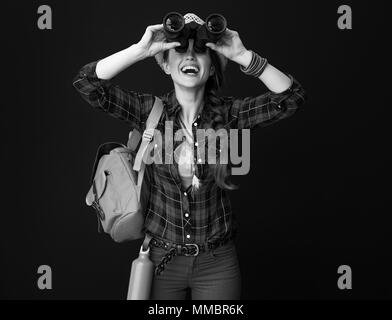Searching for inspiring places. happy fit tourist woman with backpack looking up through binoculars on background - Stock Photo