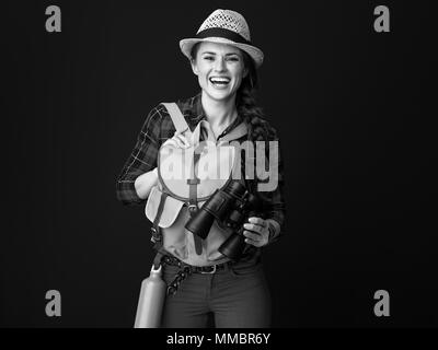 Searching for inspiring places. happy active tourist woman in a plaid shirt holding binoculars on background - Stock Photo