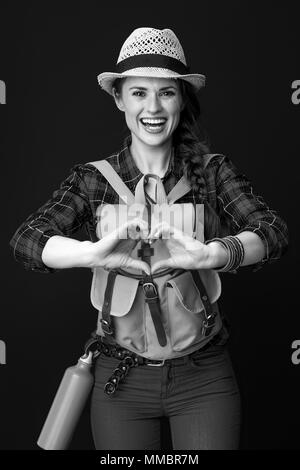 Searching for inspiring places. smiling young traveller woman with backpack showing heart shaped hands isolated on - Stock Photo