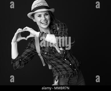 Searching for inspiring places. happy active tourist woman in a plaid shirt showing heart shaped hands against background - Stock Photo