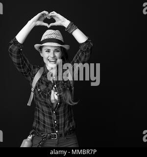 Searching for inspiring places. happy healthy traveller woman in a plaid shirt showing heart shaped hands isolated on - Stock Photo
