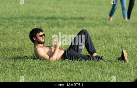shirtless mediterranean guy laying in a park - Stock Photo