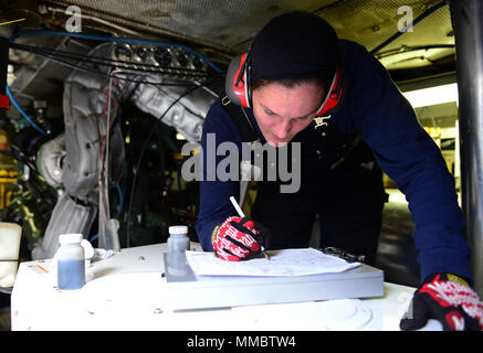 Coast Guard Petty Officer 2nd Class Kelly Yost does a round in the engine room while aboard a 55-foot Aids to Navigation Boat, Aug. 16, 2016. As a crewmember with Aids to Navigation Team Puget Sound, Yost and her shipmates maintain 129 aids to navigation in the Puget Sound region. U.S. Coast Guard - Stock Photo