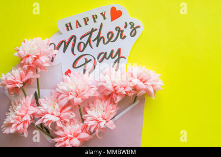 Gift box with flowers and greeting card for Mother's Day on yellow background. lisianthus, chrysanthemum flowers.Happy Mother's day concept - Stock Photo