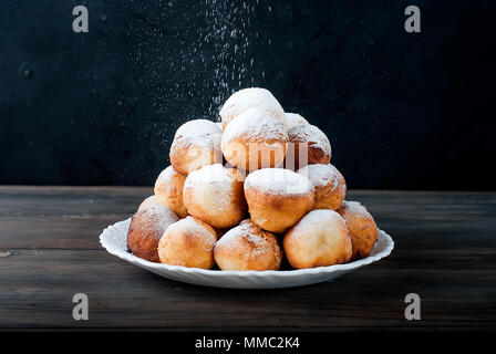 sweet donuts laid out pyramid sprinkled with powdered sugar on the plate ,on dark background , copy space - Stock Photo