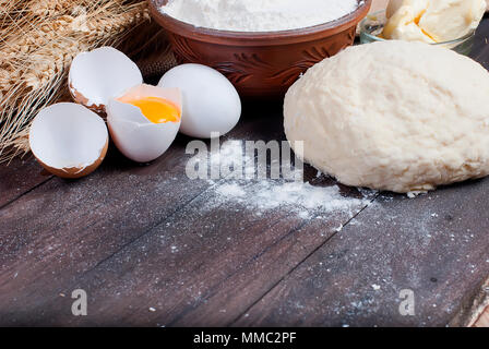 Flour in a bowl, dough, , broken egg, butter, ears. ingredients for baking on the old wooden table, top view, copy space - Stock Photo