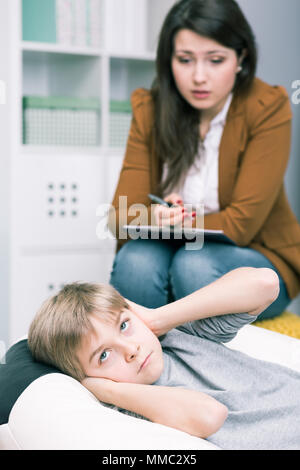 Boy covering ears with hands and teacher during private lesson - Stock Photo