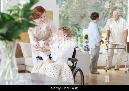 Friendly nurse gives a cup of tea to disabled woman on wheelchair in senior home - Stock Photo