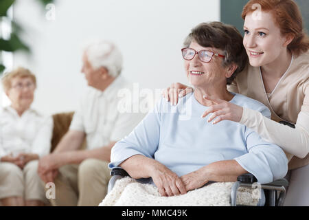 Assistant shows something to the patient on wheelchair in senior home - Stock Photo