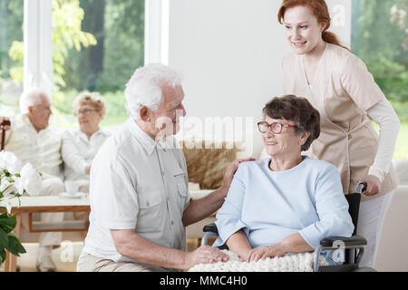 Nurse supports disabled senior woman on wheelchair during meeting with visitor - Stock Photo