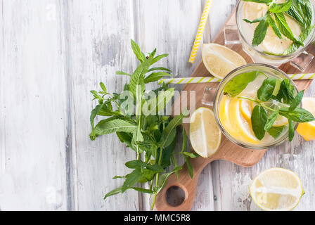 Fresh homemade lemonade in glass with ice and mint, ingredients for cocktail, lemon and lime slices, mint leaves on white wooden table, copy space - Stock Photo